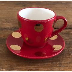 Xicara de chá vermelha com bolas douradas